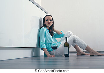 An emotionless woman sitting on the kitchen floor with a...
