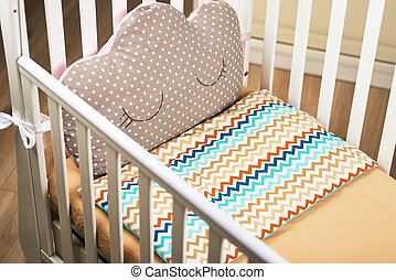 An empty baby white crib with a cute brown pink pillow with a can. brown mattress. Cozy bed for the baby