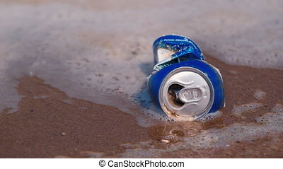 An empty beer can in the dirty water. Water pollution - An...