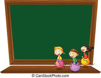 An empty blackboard with three playful kids