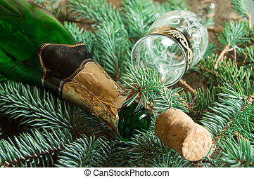 An empty bottle of champagne, a cork and a wine glass lying on spruce branches, focus on the neck of the bottle, Christmas background