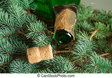 An empty bottle of champagne and a cork lying on spruce branches, focus on the neck of the bottle, Christmas background