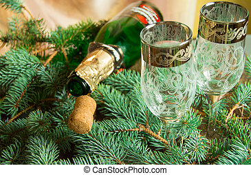 An empty bottle of champagne and a cork lying on spruce branches, near two wine glasses, focus on the tube, Christmas background