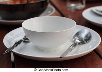 An empty cup with plate, fork and spoon on a wooden table
