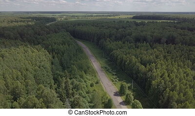 an empty road in the woods. Flight up over river. Aerial landscape