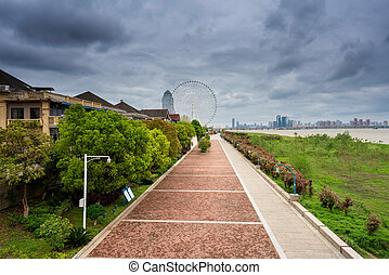 An empty road under the ferris wheel in a city park