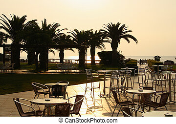 An empty seaside hotel. Street cafe on the background of palm trees at dawn.