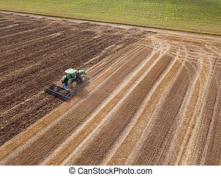 An endless agricultural field after harvesting with tractor on it . Cultivation of the soil by a tractor for sowing works.