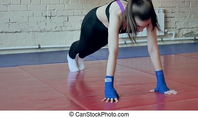 An energetic woman in boxing in the gym, coaches in elastic...