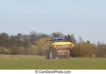 spreading fertiliser - an english landscape with a tractor...