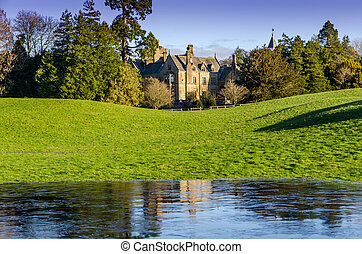 An English mansion with frozen water in the foreground.