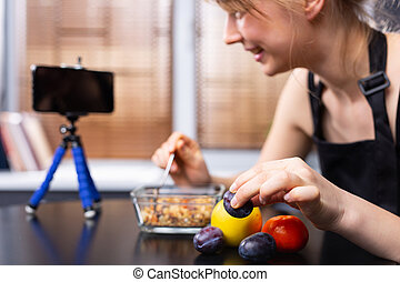 An enlarged photo of a food blogger girl in front of the phone camera with cereals and fruits on a blurred background. The concept of stream blogging and proper nutrition. High quality photo