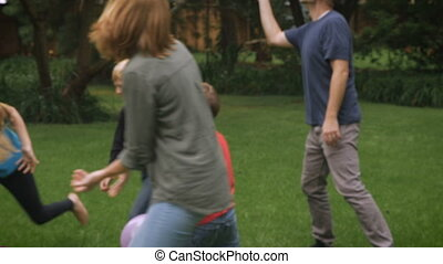 An entire family of five play together outside jumping and...