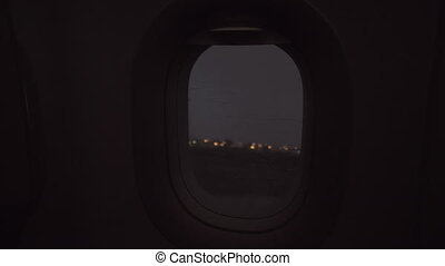An evening rainy view from an airplane porthole - A gloomy...