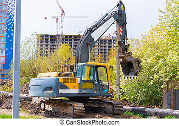 An excavator stands on heaps of soil during the construction of the road against the background of multi-storey buildings under construction.