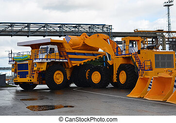 An excavator with a bucket produces an imitation of loading sand into a large mining truck. Big Truck Show. View of the parking lot of an exhibition of large career heavy dump trucks at the automobile plant Belaz in the Republic of Belarus. Zhodino .
