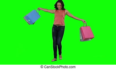 An excited woman is holding shopping bags