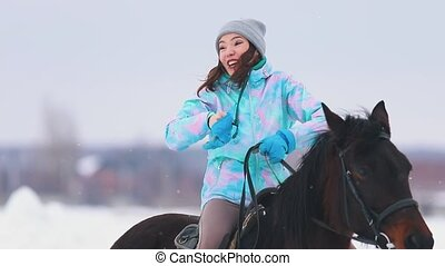 An excited young woman on a horseback talking to her friend