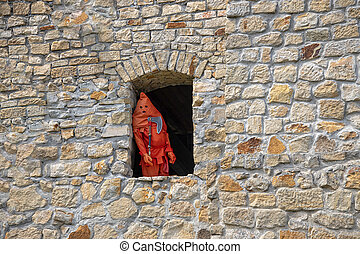an executioner dressed in red standing in the window of a  castle