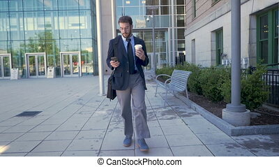An executive millennial businessman walking and browsing on...