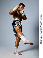 An experienced fighter kickboxer with a raised foot.
