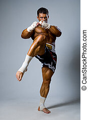 An experienced fighter kickboxer with a raised foot. full height.