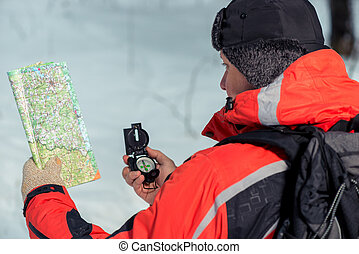 An experienced tourist with a map and a compass in the winter forest