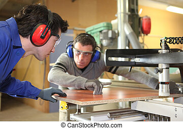 An experienced worker showing an apprentice how to cut a ...