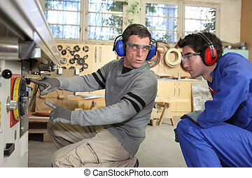 An experienced workman showing an apprentice the ropes