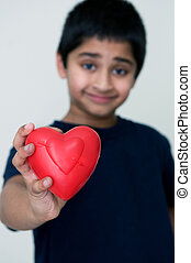 an handsome Indian kid holding out a red heart