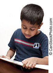 an handsome Indian kid reading his homework