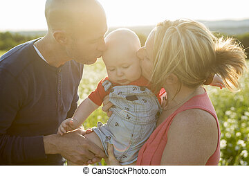 happy family of three. Father, mother and baby playing outside in summer at sunset time.