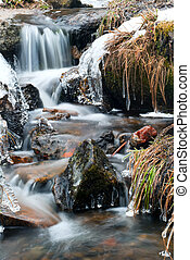 icy stream - an icy stream running through rocks and grass