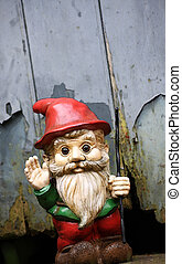 An illustration of a small bearded garden gnome with a red peeked hat waving its hand and holding a staff. Set at a slight angle against a shed door with peeling paint. Copy space avilable.