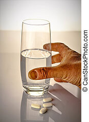 An image of a glass water with pills