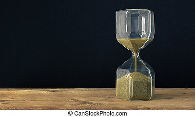 a hourglass on a wooden underground with black background