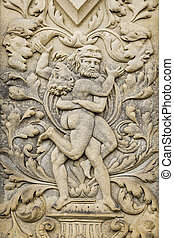 a sand stone relief of two men fighting