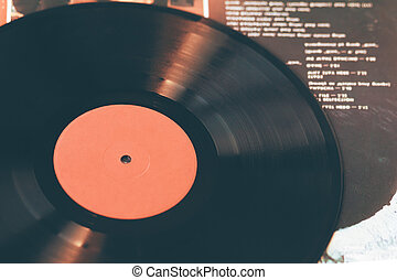 An image of a vinyl record that lies on the paper cover of a music album.