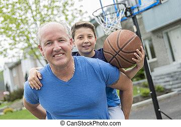 Image of man and his son playing basketball