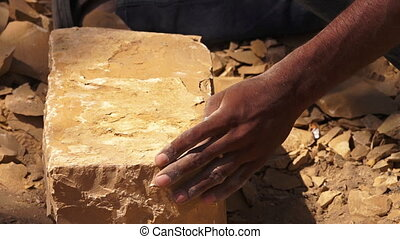An Indian man hammering a stone block - A low angle close up...