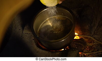 An Indian pouring salt into a metal pot on an open flame