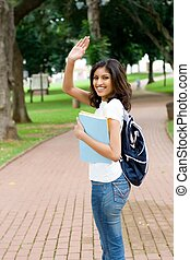 waving goodbye - an indian student waving goodbye to friends