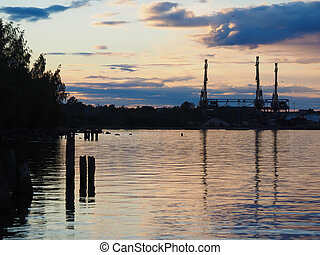 an industrial city on the shore of lake at sunset