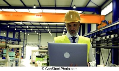 An industrial man engineer standing in a factory, using laptop.