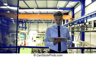 An industrial man engineer standing in a factory, using...