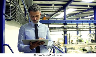 An industrial man engineer standing in a factory, using tablet.