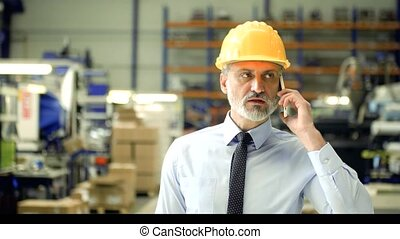 An industrial man engineer with smartphone in a factory, making a phone call.