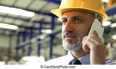 An industrial man engineer with smartphone standing in a factory, making a phone call.