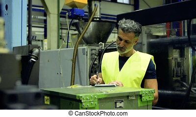 An industrial man worker standing in a factory, writing.