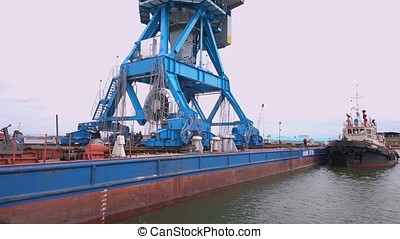 An industrial railroad terminal with gantry cranes and railroad container cars. Large cranes in sea. Shore crane lifts container during cargo operation in port in action. Timelapse